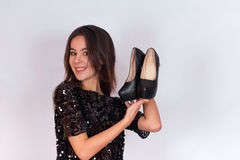 Beautiful brunette girl in a black dress holding black high-heeled shoes. Royalty Free Stock Photos