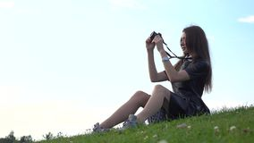 Beautiful brunette girl in black dress sitting on the lawn and making photos with her camera. Amateur photographer Stock Photos