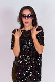 Beautiful brunette girl in a black dress and sunglasses. Brunette with long black hair Stock Photography