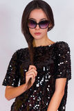 Beautiful brunette girl in a black dress and sunglasses. Brunette with long black hair. Royalty Free Stock Photo