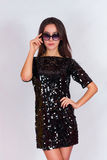 Beautiful brunette girl in a black dress and sunglasses. Brunette with long black hair Royalty Free Stock Photos