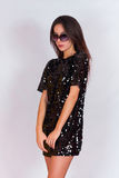 Beautiful brunette girl in a black dress and sunglasses. Brunette with long black hair Royalty Free Stock Images