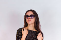 Beautiful brunette girl in a black dress and sunglasses. Brunette with long black hair Royalty Free Stock Photography