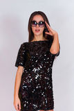 Beautiful brunette girl in a black dress and sunglasses. Brunette with long black hair Stock Photo