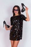 Beautiful brunette girl in a black dress and sunglasses, holding black high-heeled shoes. Stock Images