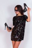 Beautiful brunette girl in a black dress and sunglasses, holding black high-heeled shoes. Royalty Free Stock Photography