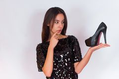 Beautiful brunette girl in a black dressholding black high-heeled shoes. Royalty Free Stock Photos