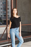 Beautiful brunette girl in a black T-shirt and mom jeans on the street Royalty Free Stock Photography