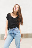 Beautiful brunette girl in a black T-shirt and mom jeans on the street Stock Photo