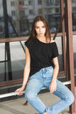 Beautiful brunette girl in a black T-shirt and mom jeans on the street Royalty Free Stock Photo