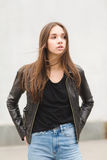 Beautiful brunette girl in a black T-shirt and mom jeans on the street. Woman in leather jacket posing outdoors royalty free stock photos