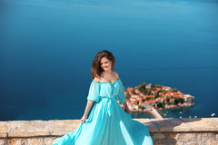 Beautiful brunette Girl in blowing dress. Happy Smiling Young Wo Royalty Free Stock Photography