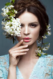 Beautiful brunette girl in blue dress with a gentle romantic make-up, pink lips and flowers. The beauty of the face. Royalty Free Stock Photography
