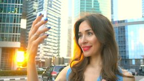 Beautiful brunette girl in blue dress making selfie at sunset against skyscrapers. 4K clip stock video footage