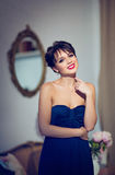 Beautiful brunette girl in a blue dress smiling in interiors.  Royalty Free Stock Images