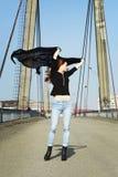 Beautiful brunette girl on the bridge. Portrait of a beautiful girl on a bridge on a sunny day Stock Image