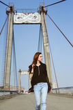 Beautiful brunette girl on the bridge. Portrait of a beautiful girl on a bridge on a sunny day Royalty Free Stock Photography