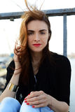 Beautiful brunette girl on the bridge. Portrait of a beautiful girl on a bridge on a sunny day Stock Images