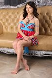 Beautiful brunette in a bright dress is sitting on a leather sofa. Beautiful brunette girl in a bright dress is sitting on a leather sofa. Pretty model lifts up Royalty Free Stock Image