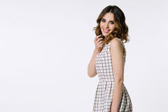 Beautiful brunette girl in checkered dress Royalty Free Stock Images