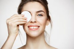 Beautiful brunette girl with clean perfect skin hiding eye behind cotton sponge smiling looking at camera over white Royalty Free Stock Photos