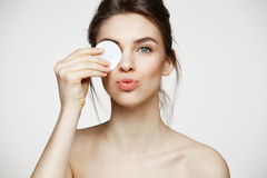 Beautiful brunette girl with clean perfect skin hiding eye behind cotton sponge smiling looking at camera over white. Beautiful natural brunette girl with clean royalty free stock photography