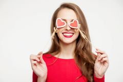 Beautiful brunette girl closed her eyes with two hearts of souvenirs. Valentine`s day concept. On white background. Place for tex. Beautiful brunette girl closed Royalty Free Stock Image