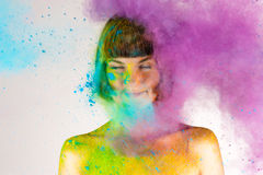 Beautiful brunette girl in colors Holi on a white Royalty Free Stock Photos