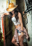 Beautiful brunette girl with country look, indoors shot in stable, rustic style. Attractive woman with cowboy hat, denim shorts Stock Images