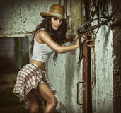 Beautiful brunette girl with country look, indoors shot in stable, rustic style. Attractive woman with cowboy hat, denim shorts Stock Image