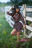 Beautiful brunette girl with country look, outdoors shot near wooden fence, rustic style. Attractive woman with cowboy hat Royalty Free Stock Image