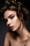 Beautiful brunette girl with a creative hairstyle and dark makeup. Art beauty, fashion model. Beauty face. Photo was made in studio Stock Photography