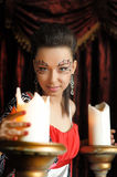 Beautiful brunette girl with creative make-up near the big candles Stock Images