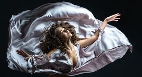 Beautiful brunette girl with curly hair in the darkness and light in silver satin flying dress awesome poses in dance royalty free stock photography