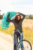 Beautiful brunette girl at cycling on dirt road Royalty Free Stock Photos