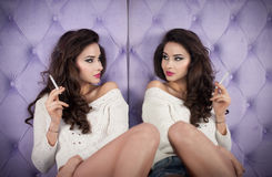 Beautiful brunette girl in denim shorts and white blouse posing on lilac textured background smoking and looking into a mirror Stock Photo