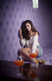 Beautiful brunette girl in denim shorts and white blouse posing  on lilac textured background with two drink glasses foreground. Young sensual woman siting Royalty Free Stock Photography