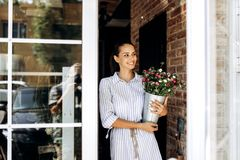 Beautiful brunette girl dressed in a striped dress holds a vase with pink and white chrysanthemums outside near the door royalty free stock images
