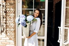 Beautiful brunette girl dressed in a striped dress smiles and and hold a vase with light blue hortensia outside near the royalty free stock image