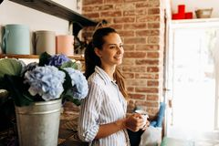Beautiful brunette girl dressed in a striped dress stands in the flower shop near the vase with light blue hortensia and stock images