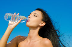 Beautiful brunette girl drinking from a bottle of Stock Photo