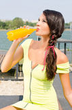 Beautiful brunette girl drinking orange juice from a plastic bottle. Stock Photo