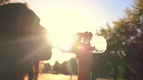 Beautiful brunette girl drinking water from plastic bottle in the park, warm sunset colors. Slow motion shot