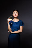 Beautiful brunette girl in evening dress posing, holding champaign glass. Royalty Free Stock Images