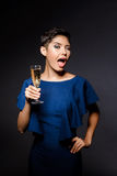 Beautiful brunette girl in evening dress winking, holding champaign glass. Young beautiful brunette girl in dark blue evening dress winking, holding champaign Royalty Free Stock Images