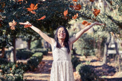 Beautiful brunette girl with falling leaves in the autumn Stock Photos