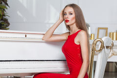 Beautiful brunette girl in a fashionable evening dress. Red lips. Studio shot Stock Image