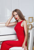 Beautiful brunette girl in a fashionable evening dress. Red lips. Studio shot