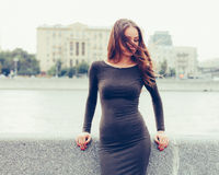 Beautiful brunette girl in fashionable dress sad at the city waterfront Royalty Free Stock Images