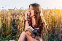 Beautiful brunette girl field. He eats an apple. Concept new ideas, outdoors, summer in nature. In his hand a notebook Royalty Free Stock Images
